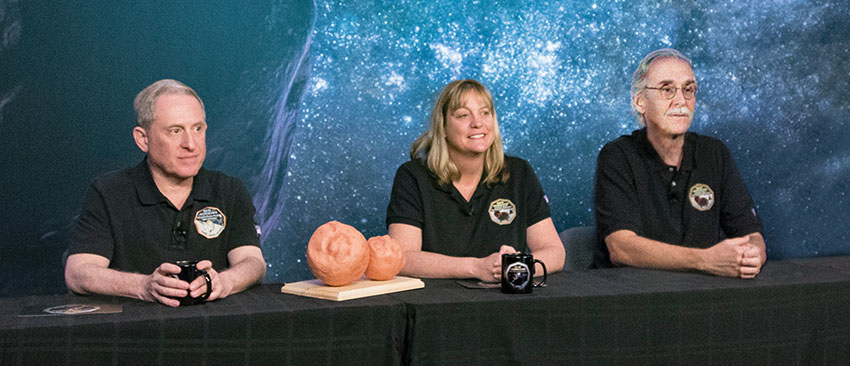 S. Alan Stern, Ph.D., Cathy Olkin, Ph.D., and John Spencer, Ph.D. sitting at a media event table