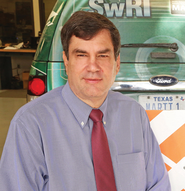 White man in dress shirt and tie sitting in front and to the left of the rear-end of a SUV