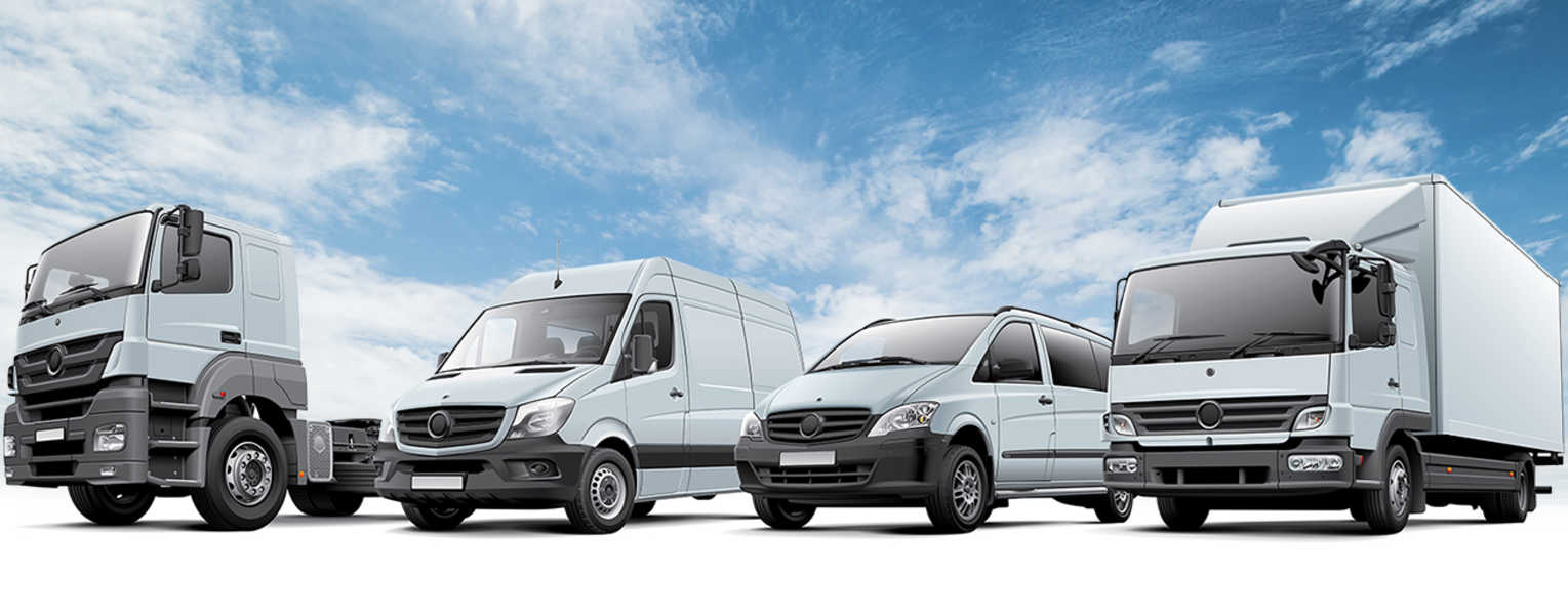 From left to right, a white semi cab, a white van, a white minivan, and a white box truck silhouetted against a blue cloudy sky