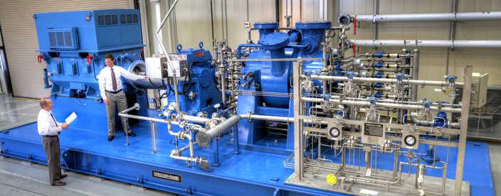Two men standing near a gas turbine compressor