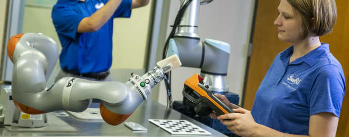In foreground, a woman using a control pad to manipulate a collaborative robot; in background, a man is working on a second robot