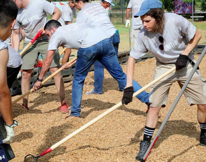 People working outside, raking woodchips