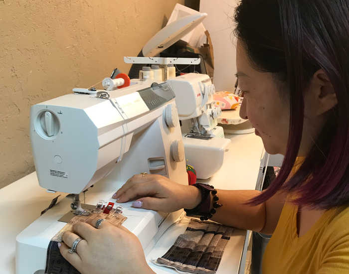 Woman bent over sewing machine sewing fabric into masks