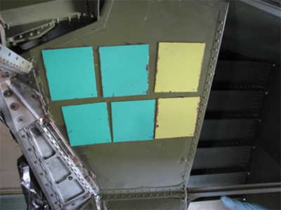 6 square pieces of sheet metal painted with military aircraft paint showing the use of biocide to prevent fungal growth