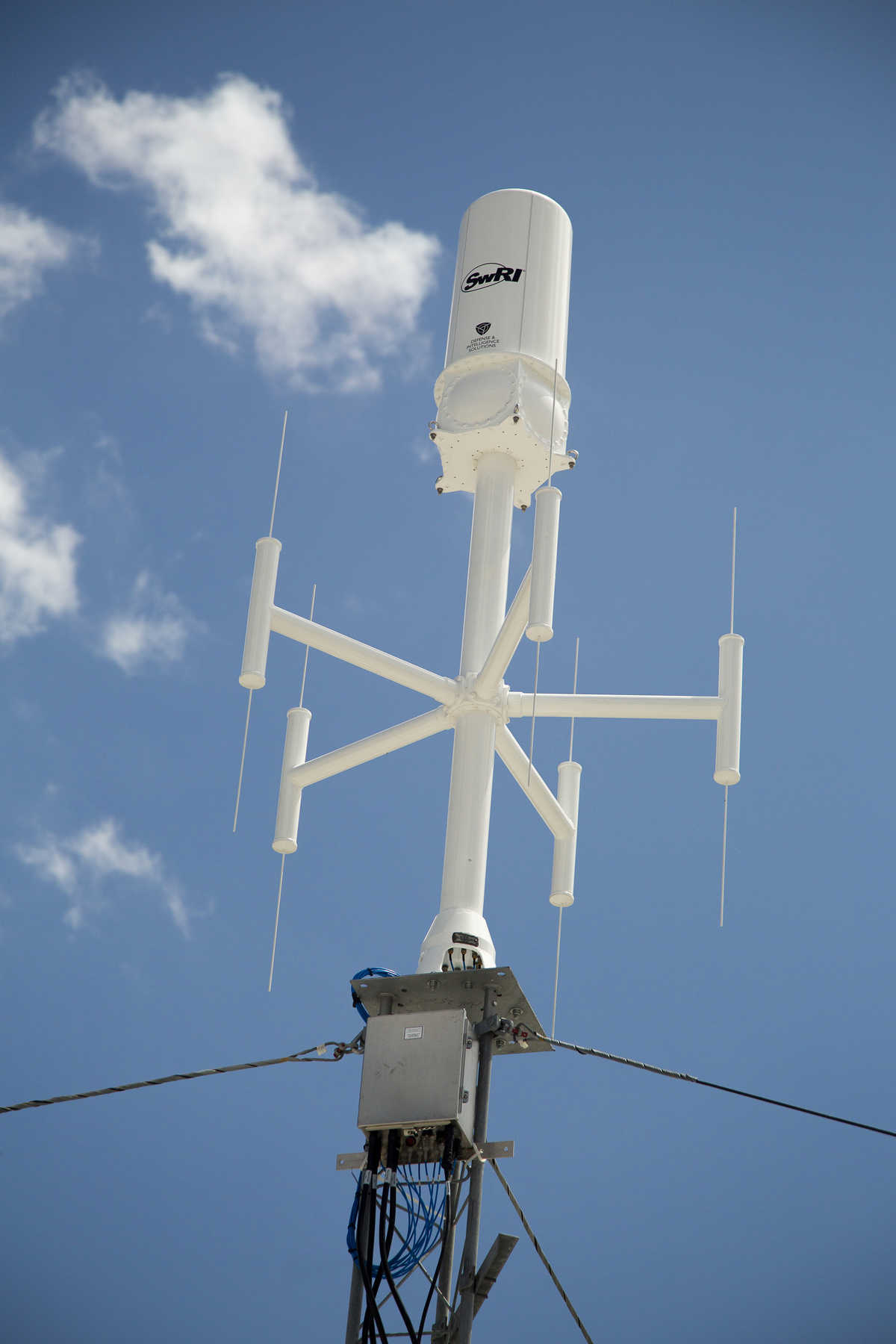 White antenna with blue sky and clouds in the background