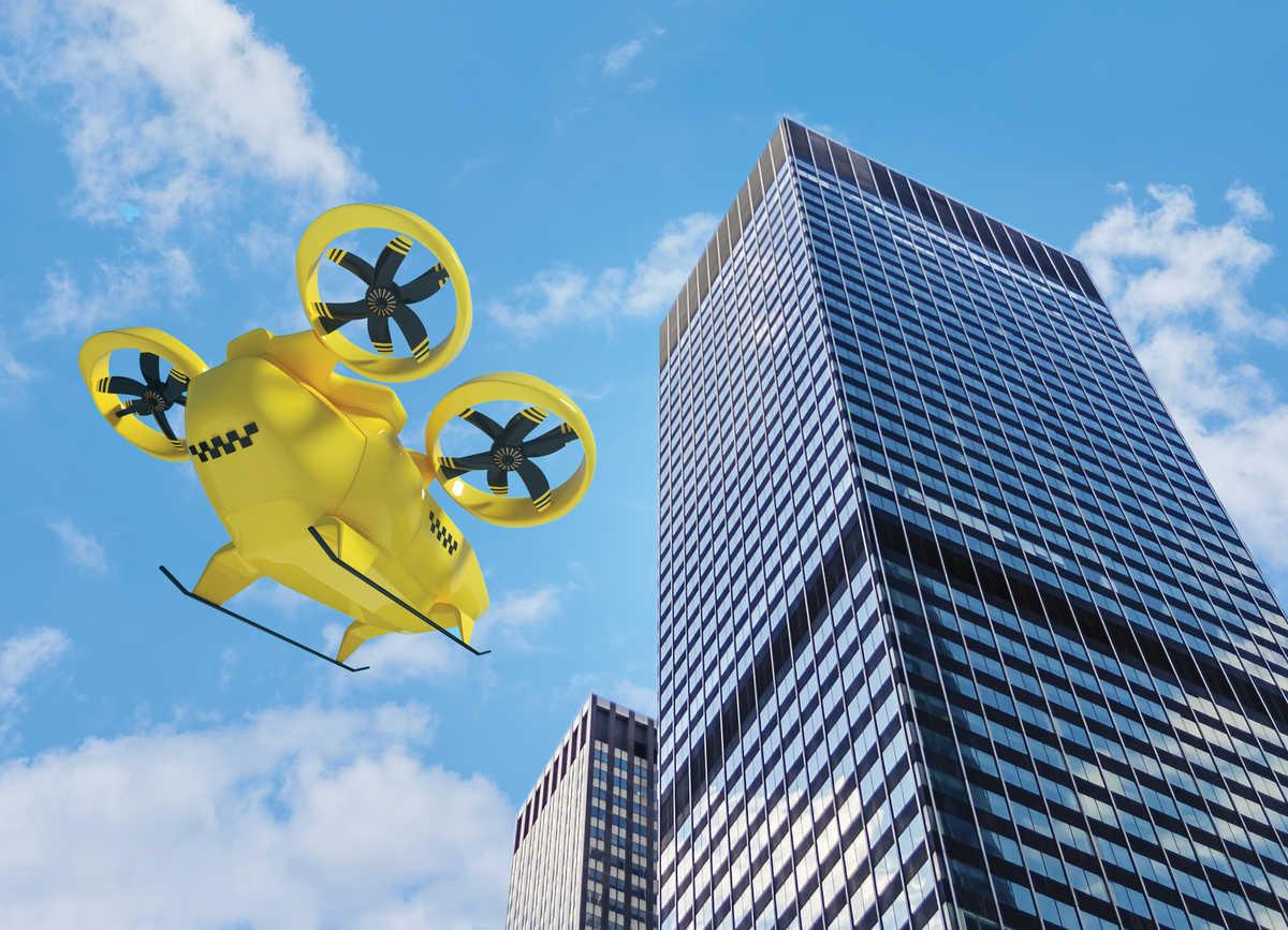 yellow air taxi heading toward multi-story building