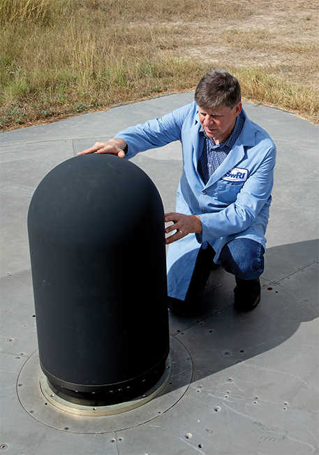 man in blue lab coat kneeling next to antenna installed on concrete pad