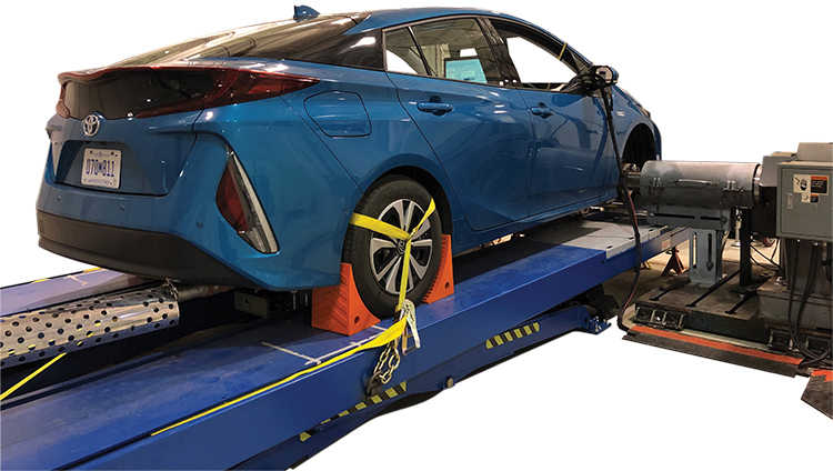 blue hybrid sedan connected to vehicle chassis dynamometer
