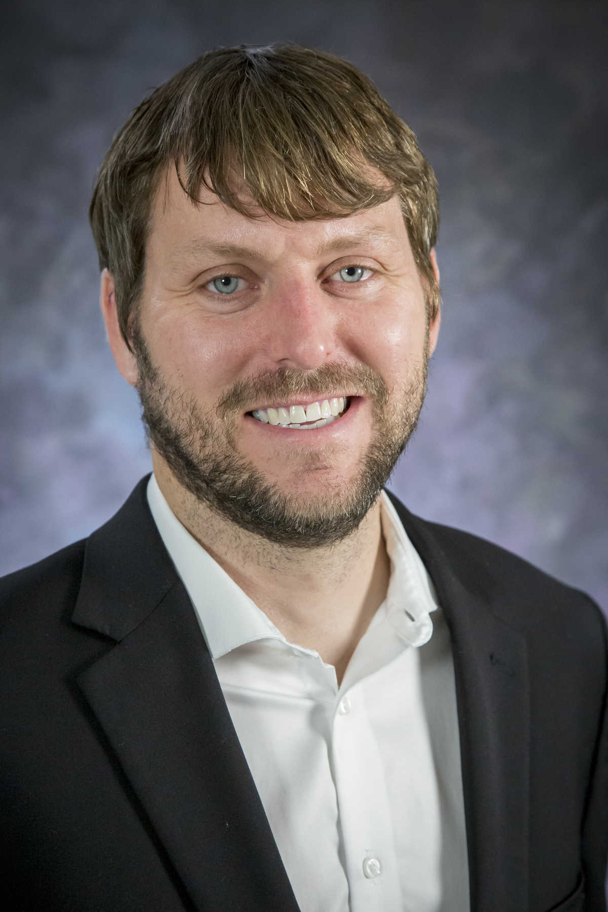 Victor Murray portrait against a blue backdrop