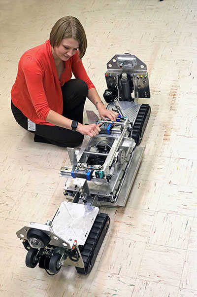 engineer looking over a robot with tank treads