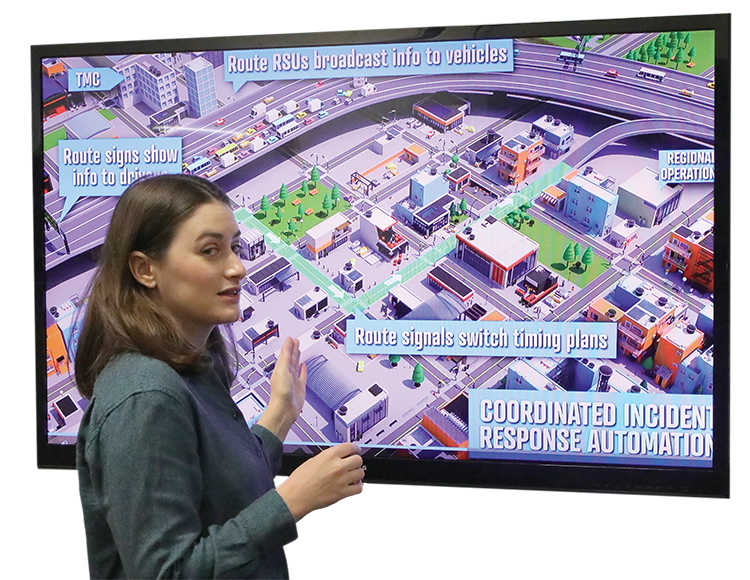 white woman standing in front of large television screen showing artist rendering of coordinated incident response automation