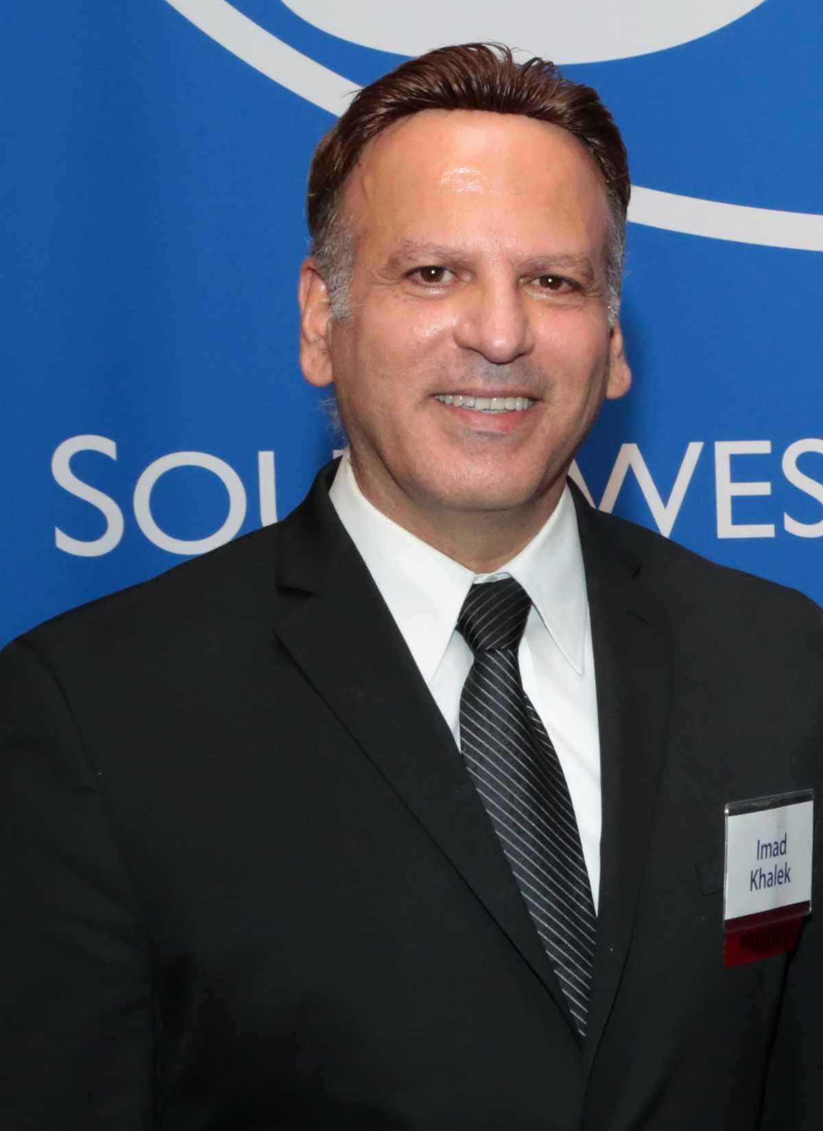 Portrait of Dr. Imad Khlaek against a blue background