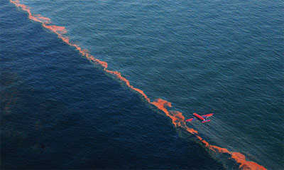 Airplane dropping dispersants on oil spill over water