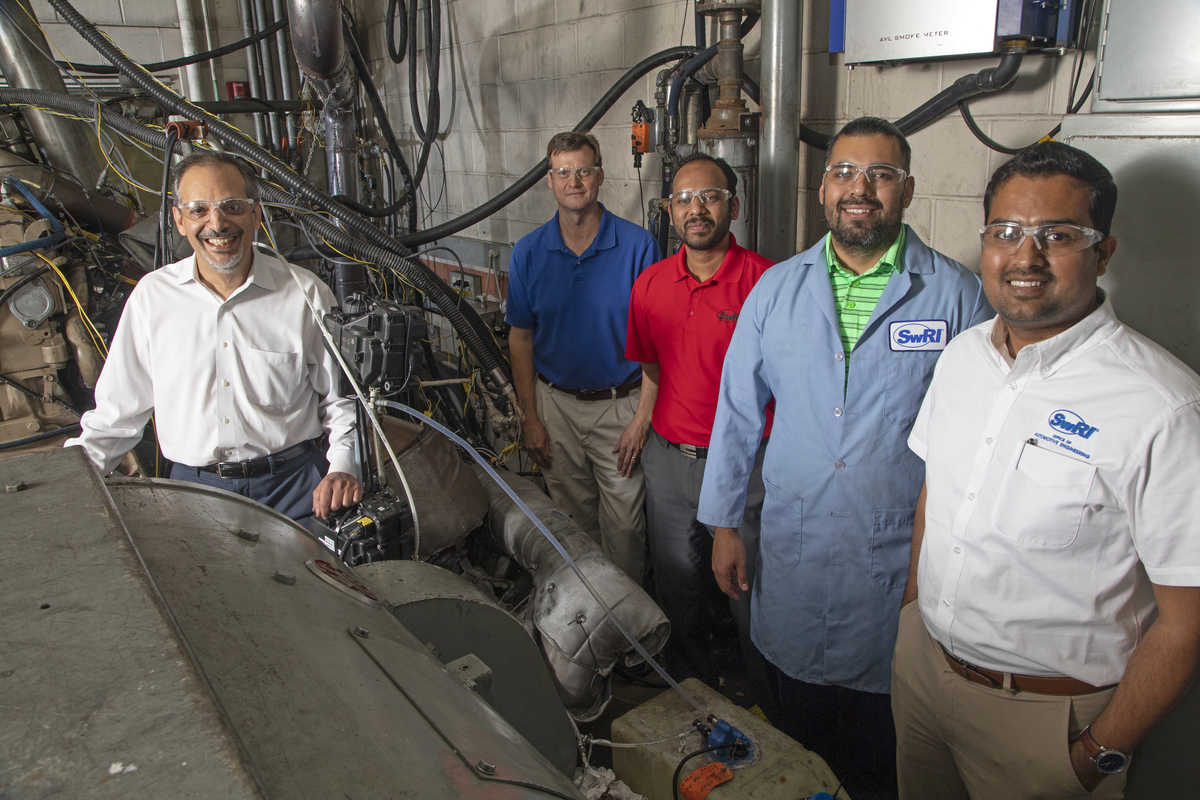 Five SwRI engineers posed smiling around a diesel stand in a lab