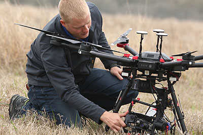 Technician inspecting a drone in a field