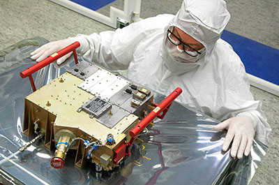 UVS instrument with red handles on a clean room table with an engineer standing by