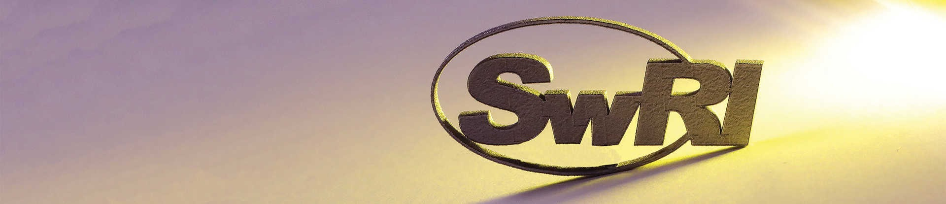 SwRI logo cut from a titanium block with a shadow falling on the left side