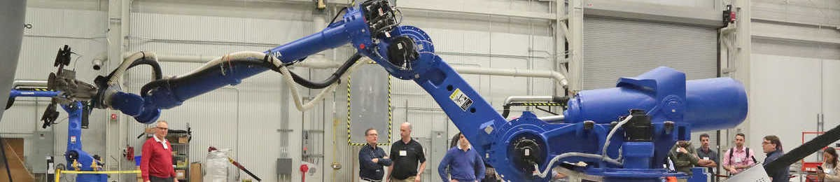 Engineers in a lab demonstrating a blue robot