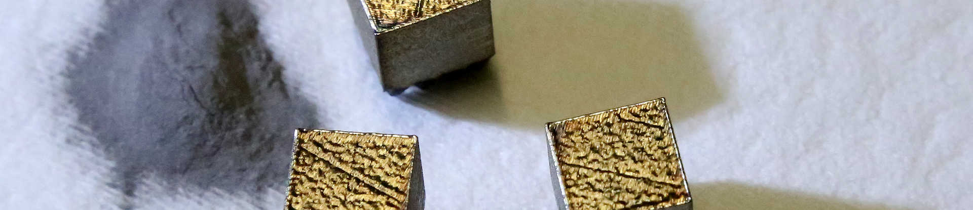 Metal powder in a pile on the left, three small metal cubes on the right