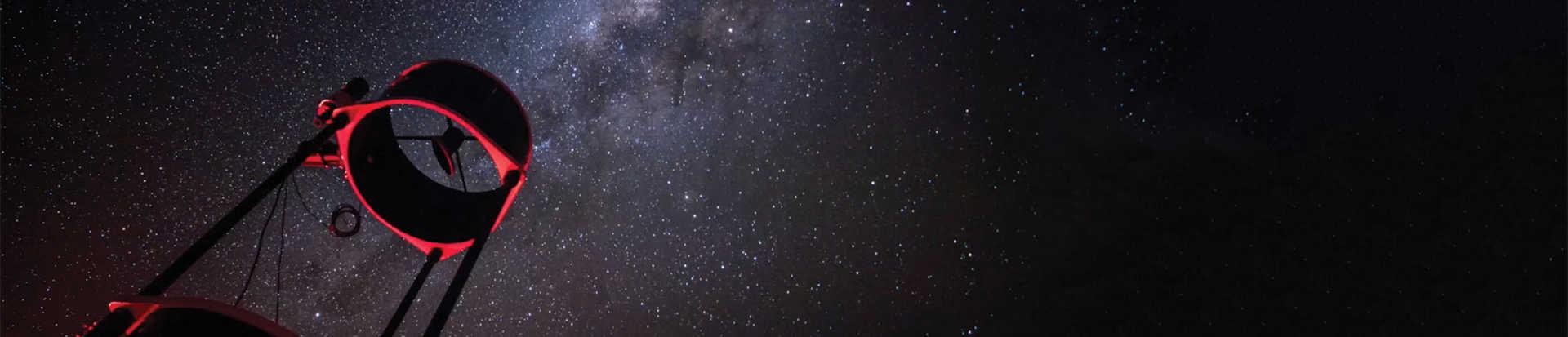Telescope against starry night sky
