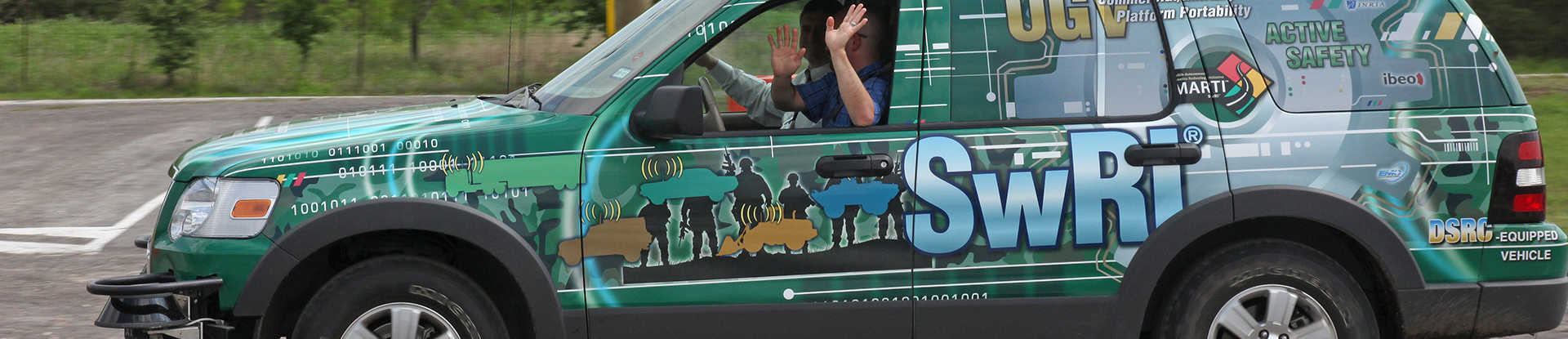Driver with hand off steering wheel of SUV covered in vinyl graphics