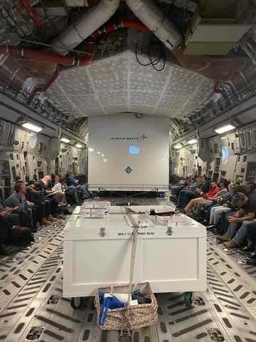 The Lucy spacecraft shipping container aboard a U.S. Air Force C-17 cargo plane accompanied by a few team members