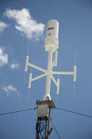 White antenna with five poles with blue sky in the background