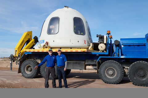 Engineer Kevin Supak and engineer Steven Green standing in front of part of Blue Origin's New Shepard vehicle