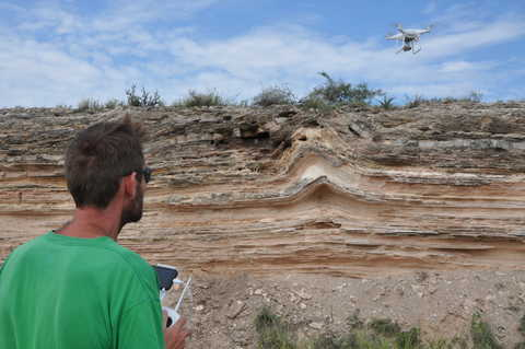 an engineer in a green shirt flying a drone over varied terrain