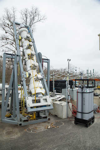 A metal gas foam test stand set up outdoors for testing