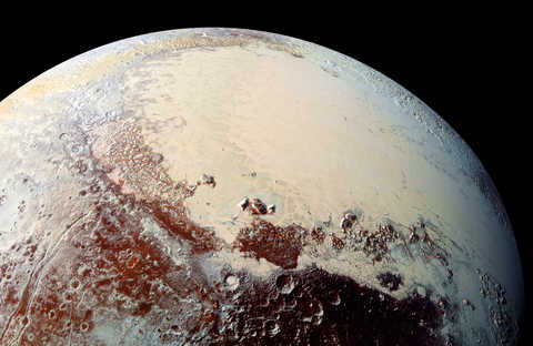 Pluto's surface shows a remarkable range of subtle colors, digitally enhanced in this view to a rainbow of pale blues, yellows, oranges, and deep reds.