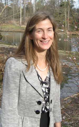 Dr. Robin Canup standing in a park next to a blooming tree