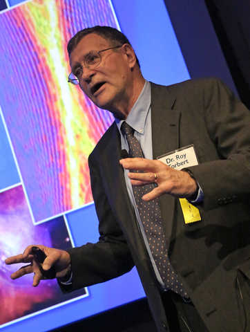 Portrait of Roy Torbert in front of a presentation screen talking to a crowd