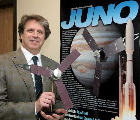 Dr. Scott Bolton standing in front of a JUNO poster holding a replica of the spacecraft