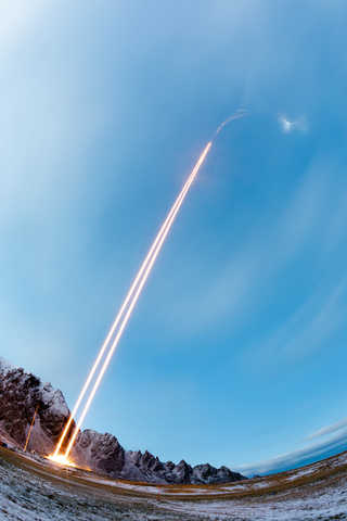 Two rocket vapor trails going up into a blue sky