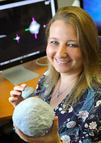 Dr. Tracy Becker holds models of asteroids