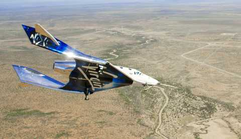 White and blue spacecraft flying over terrain