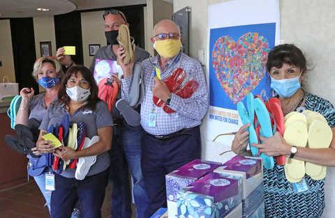 three women & 2 men holding flip-flops for donation