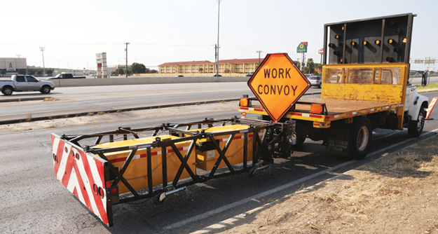 Truck with work convoy sign and directional arrow pointing left