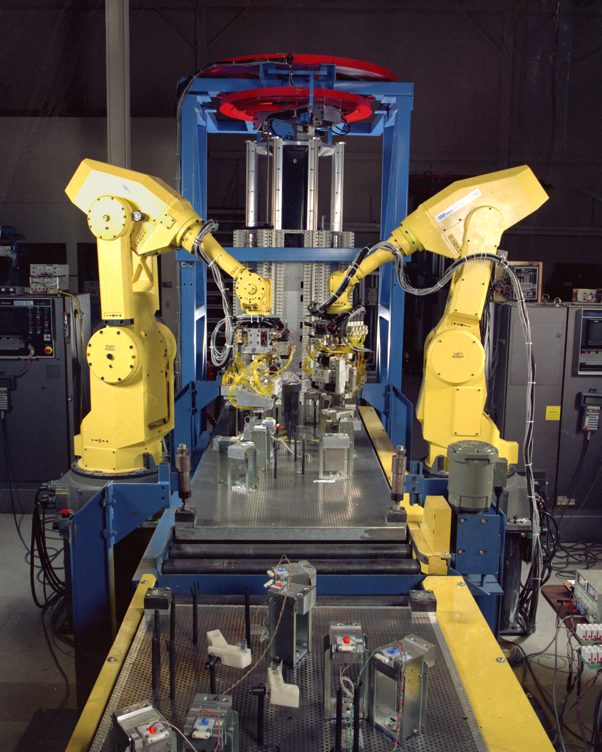 Two yellow robotic arms building components