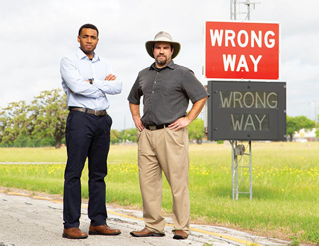 """Authors standing next to """"wrong way"""" street signs"""